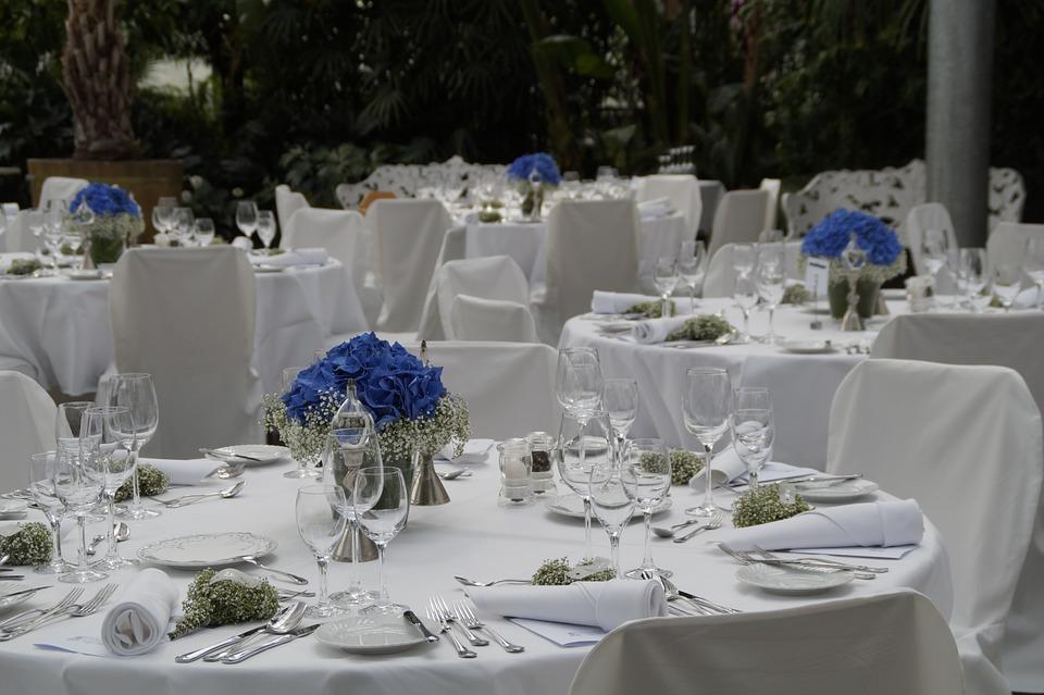 Hochzeitslocation klassisch eingedeckt mit runden Tischen und Hussen