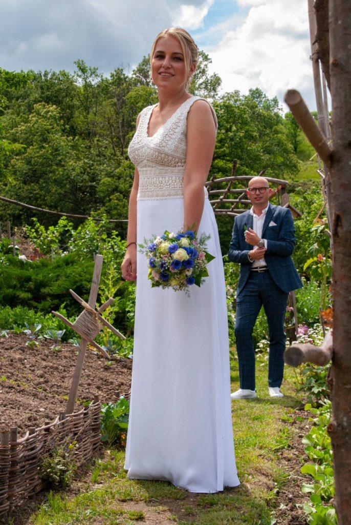 Braut und maßgeschneidertes Brautkleid im Vordergrund, Bräutigam im Hintergrund