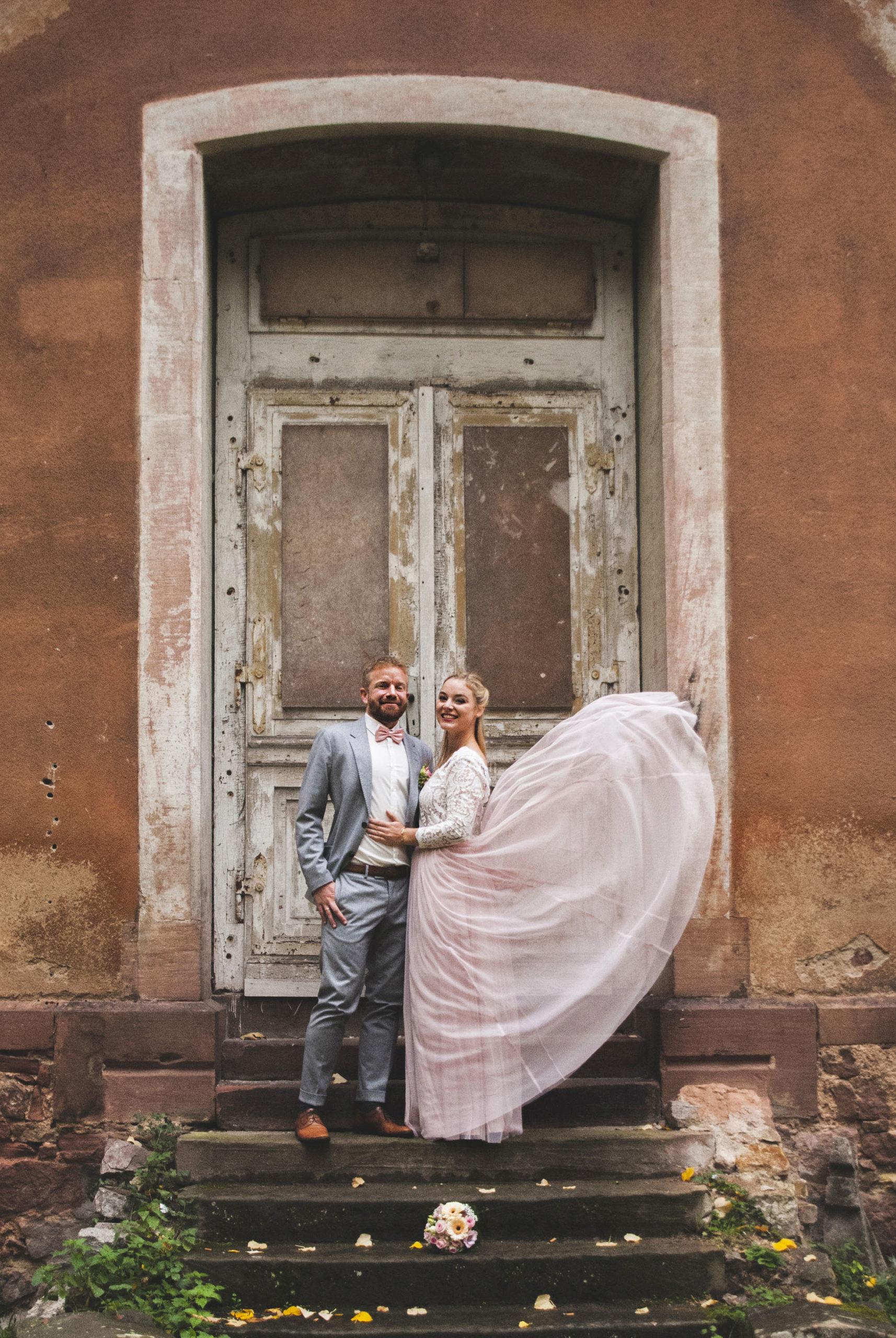 Brautpaar vor Holztür mit Windeffekt