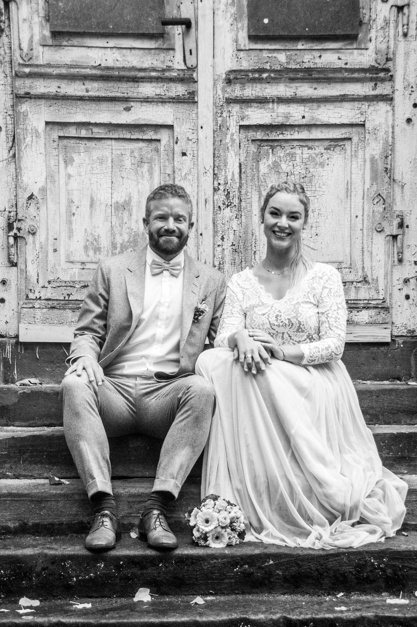 Brautpaar auf Treppe sitzend vor Holztür (schwarz-weiß)