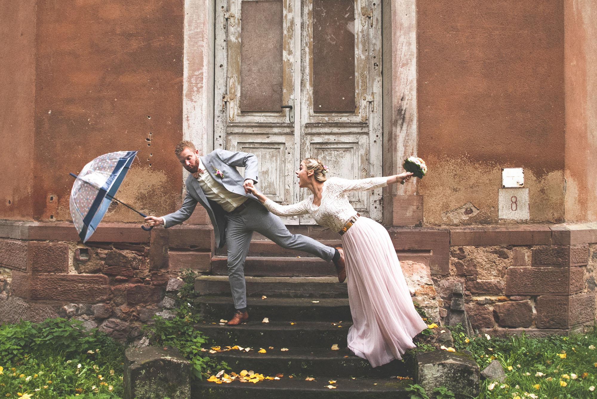 Spaßfoto Brautpaar mit Schirm im Regen