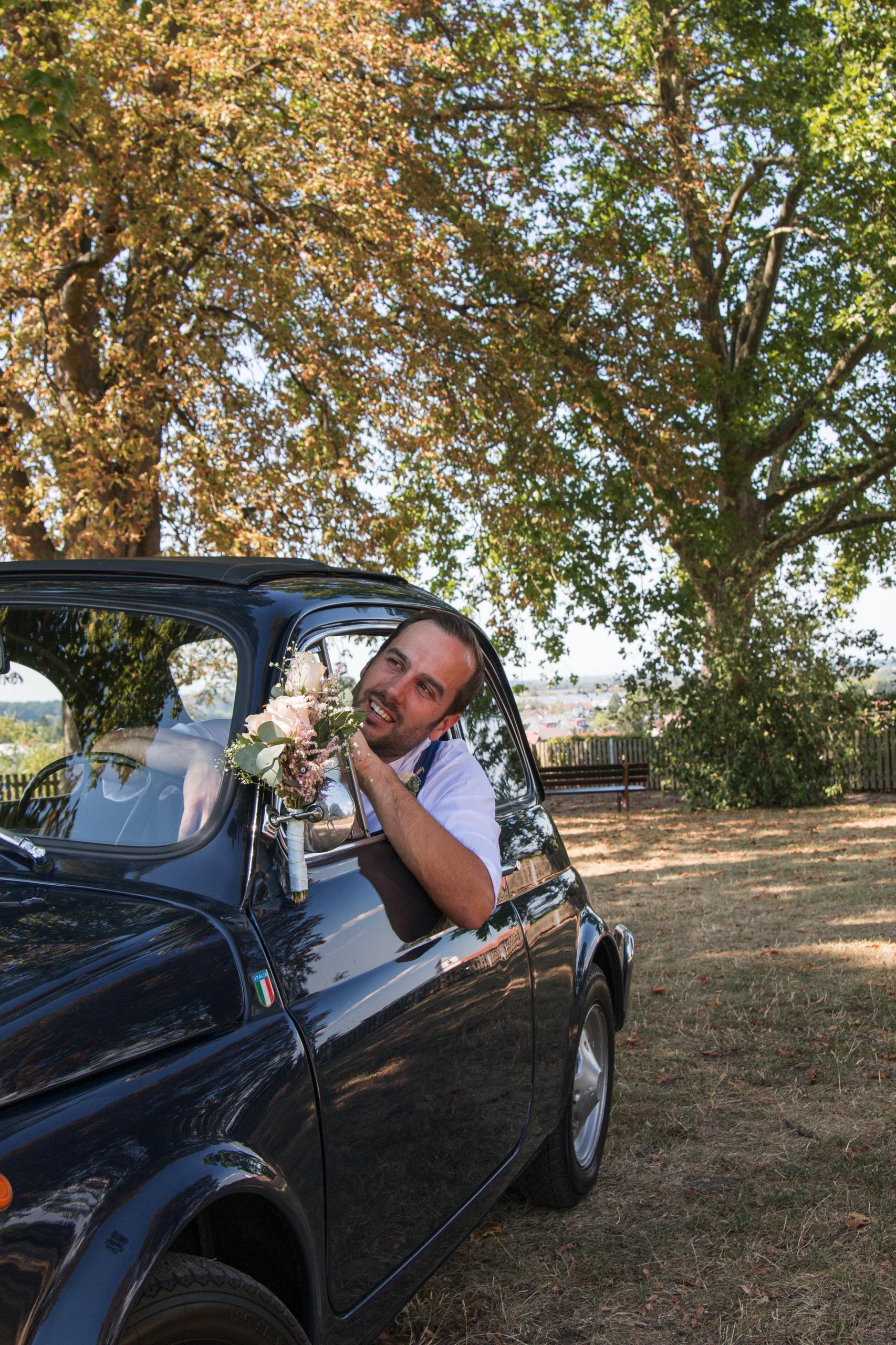 Bräutigam im Hochzeits-Fiat